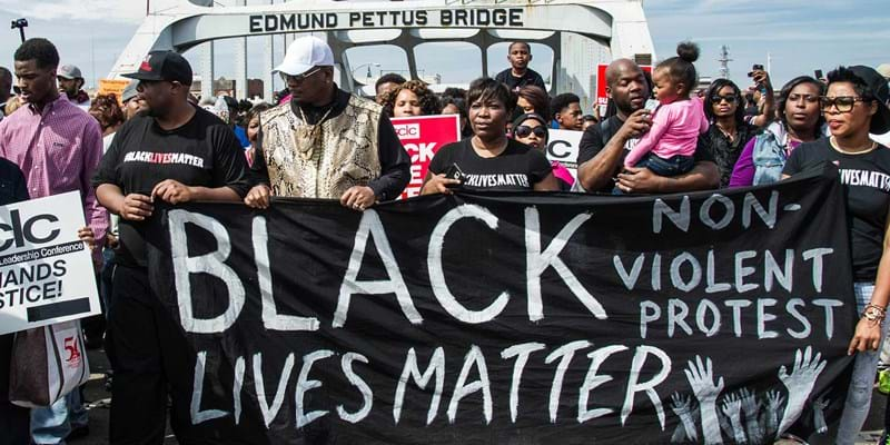 People walk across the Edmund Pettus Bridge during the 50th anniversary commemoration of the Selma to Montgomery civil rights march on March 8, 2015 in Selma, Alabama. 2015. Photo Credit & © Amy N Harris