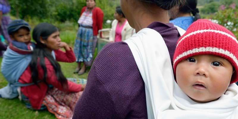 A small Maya Mam child hangs out on its mother's back during a workshop in Comitancillo, Guatemala. 2014. Photo Credit: ©Paul Jeffrey.