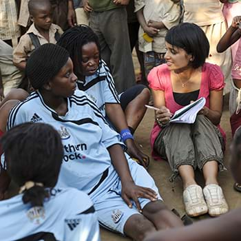 Sasha Kasthuriarachchi in discussion with a woman's football team. Photo Credit: ©Matthew Oldfield.