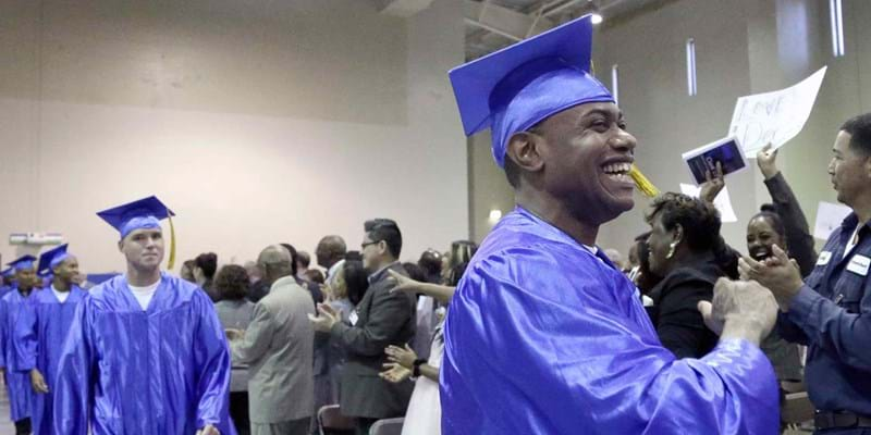 Incarcerated people in caps and gowns in the Prison Entrepreneurship Program marching toward the stage for graduation ceremonies, at the Cleveland Correctional Facility in Cleveland, Texas.  2014. Photo Credit & (c): Pat Sullivan/AP
