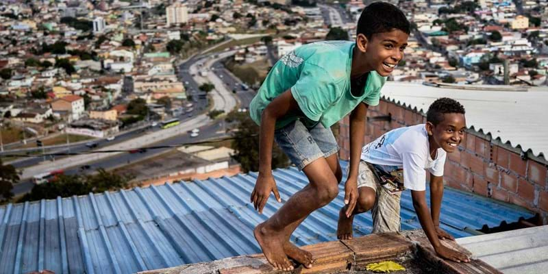 Young boys play on the rooftop of a favela. Belo Horizonte, Brazil. 2014. Photo Credit: Zackary Canepari/Panos