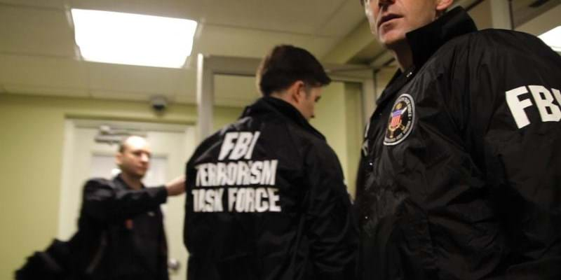 "Agents in FBI jackets in hallway. Still from ""(T)error"". 2016. This image is not available under the 4.0 Creative Commons license."