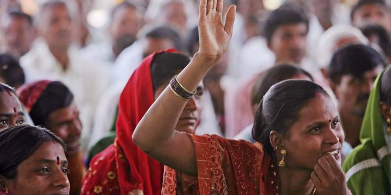 A woman raises her hand to speak at a community meeting in Aurangabad. India. 2009. Photo credit: Simone D. McCourtie / World Bank
