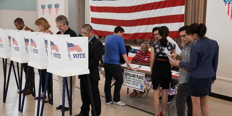 People voting in polling place. 2011. Photo credit: Blend Images LLC/Newscom