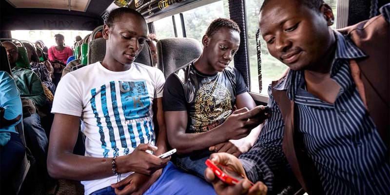 Nairobians using the internet on their smart phones as they ride on a city bus. Kenya. 2016. Photo credit: Sven Torfinn/PANOS