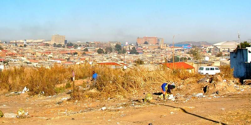Photo of residents and slums of Soweto against a backdrop of houses in Johannesburg. Photo credit: Flickr user: Jessica Eriksson