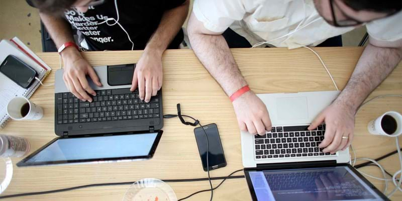 Miguel Chateloin  (L) and Lazaro Gamio use their computers to write code during the Hackathon for Cuba.  The hackathon brought together experts and programmers to devise innovative technology solutions aimed at strengthening communications and information access in Cuba. The event is organized by Roots of Hope with support from the John S. and James L. Knight Foundation. 2014. Miami, Florida. Photo credit: Getty Images