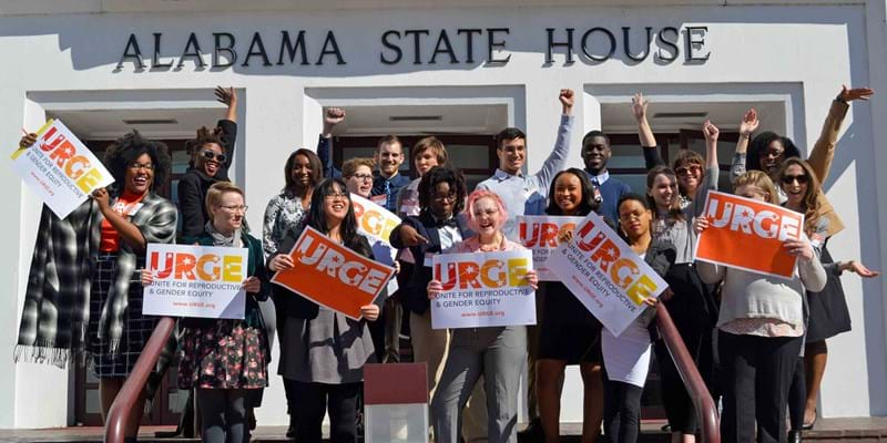 "URGE's Kierra Johnson and supporters holding ""URGE"" signs in front of the Alabama State House."