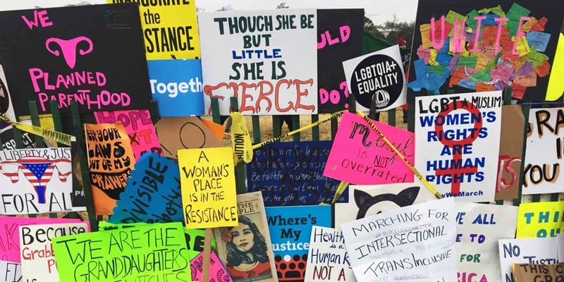 Signs from the Women's March on Washington hanging on a fence. Photo credit: Ford Foundation
