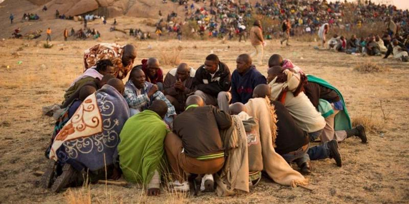 Miners in Marikana huddle and strategize during their strike for a living wage in 2012. Credit: Greg Marinovich