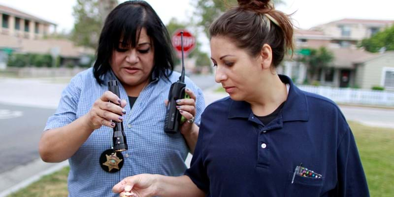 Orange County Deputy Probation Officer Erin Merritt (R) holds a spoon with black tar heroin which she found in a probationer's apartment, as she walks back to the car with Deputy Probation Officer Christine Torres in Santa Ana, California July 22, 2011. REUTERS/Lucy Nicholson