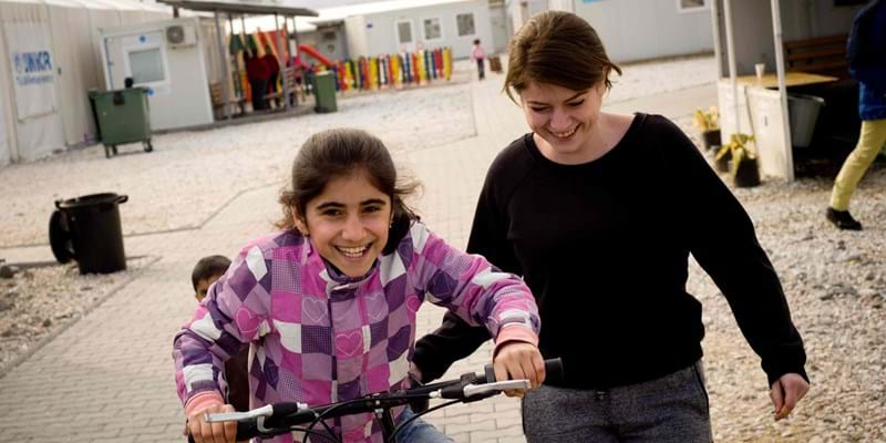 A teacher of the Temporary Transit Center of Gevgelija in south Macedonia helps a refugee girl ride a bike.
