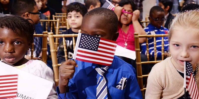 Children wave American flags after taking the Oath of Allegiance as they become U.S. citizens at a ceremony in New York. Credit: Anthony Behar/Sipa USA
