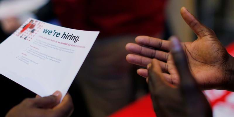 "A job seeker holds a ""We're Hiring"" card at a City of Boston Neighborhood Career Fair. Credit: REUTERS/Brian Snyder"