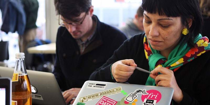 A participant puts stickers on her laptop at the 28th Chaos Communication Congress - Behind Enemy Lines computer hacker conference in Berlin, Germany. Credit: Adam Berry / Stringer