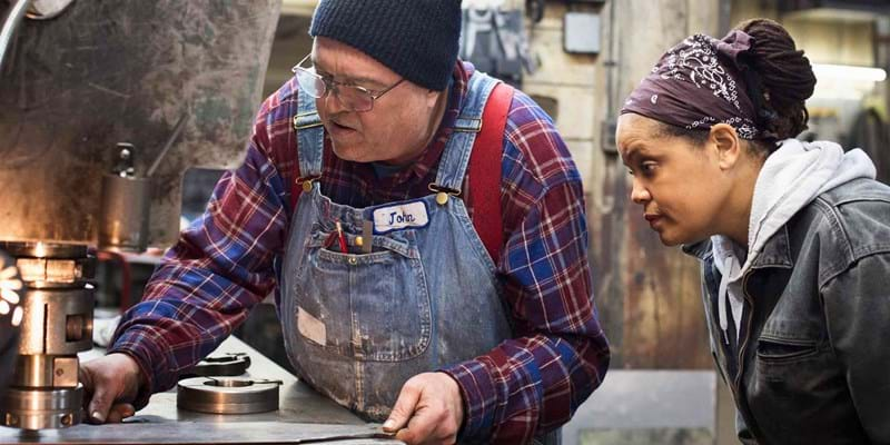 Metal shop foreman John training a young woman in his trade.