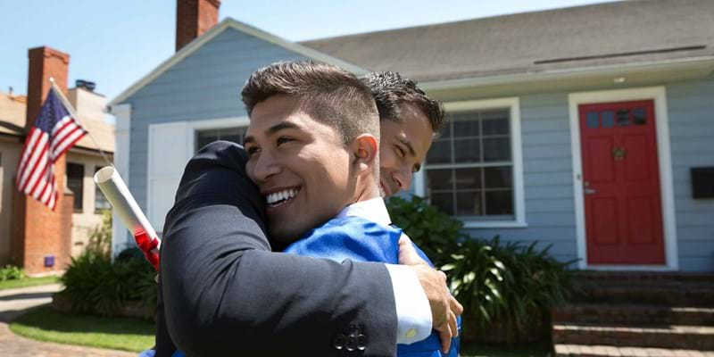 Hispanic father is hugging and congratulating his son in front of their home on graduation day.