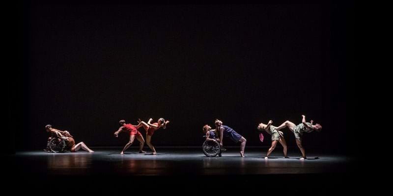 From Dancing Wheels Company & School: Four pairs of dancers are in a beam of light on a black stage; in each pair, one dancer leans on another, and two dancers are wheelchair users.