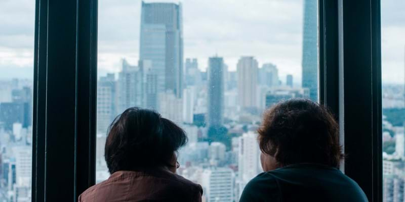 Two people staring out a skyscraper window