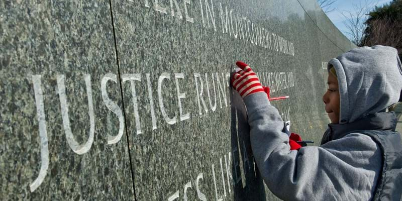 "Boy standing in front of ""The Civil Rights Memorial Center"" wall in Montgomery, Alabama."