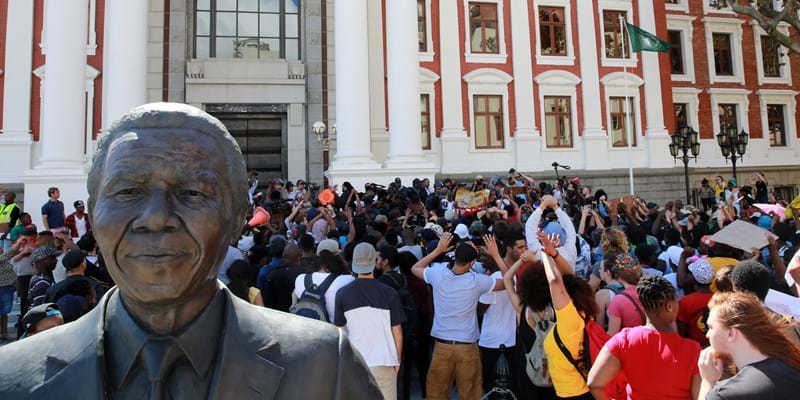 Protesting students broke through the gates of parliament during protests against a proposed hike in tuition fees (Photo by Nardus Engelbrecht/Gallo Images/Getty Images)