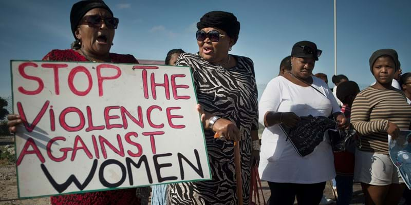 Women hold signs during a protest against ongoing violence against women, in Gugulethu, on May 21, 2016, about 20 Km from the centre of Cape Town. Credit: RODGER BOSCH/AFP/Getty Images