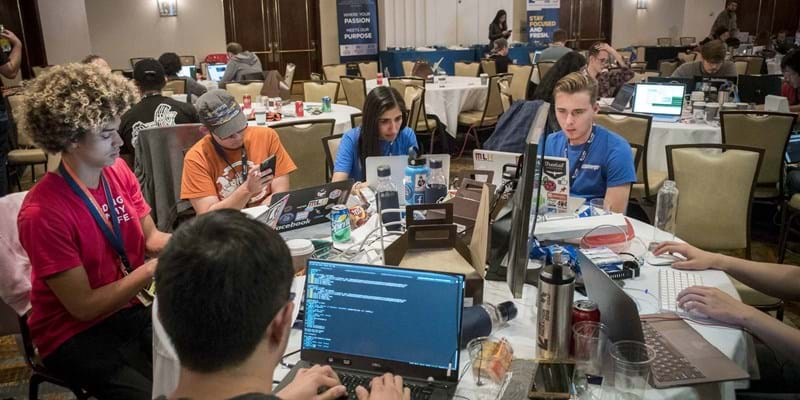Group of young people sitting at a round table on their computers participating in a hackathon.