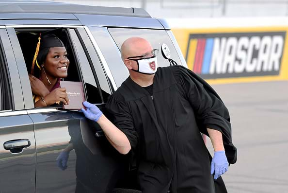 A high school principal wearing a protective  mask and gloves presents a graduate with her diploma through the car window.