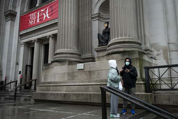 Two tourists wear protective masks while standing in front of the Metropolitan Museum of Art