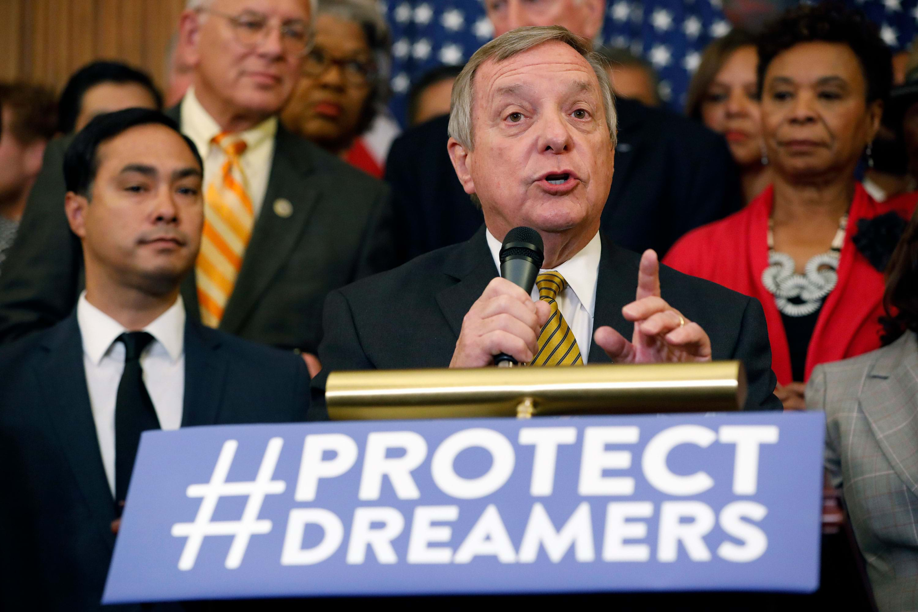 U.S. Senator Dick Durbin speaking at a podium with a sign that reads: Protect Dreamers.