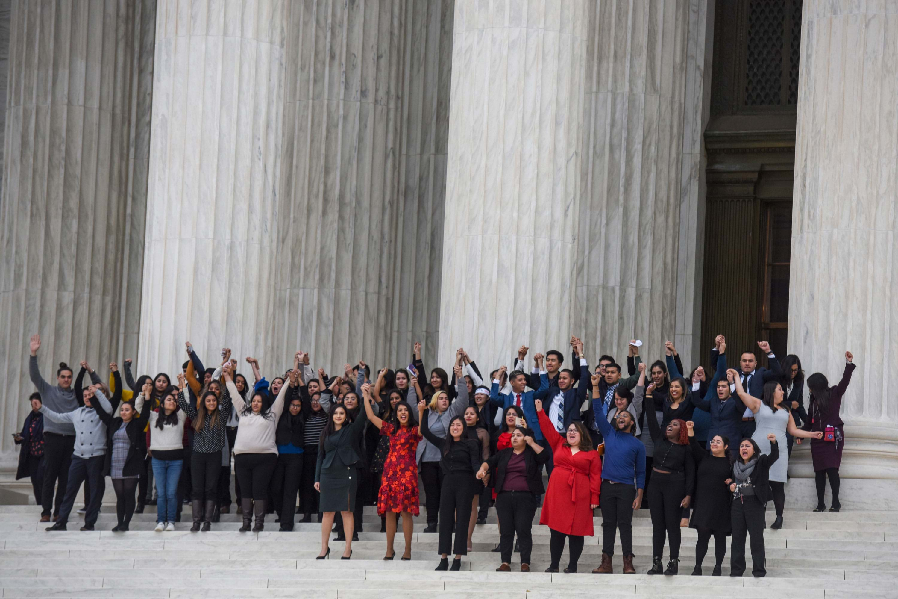 A group of people on the steps of the US Supreme Court raising their arms and cheering.