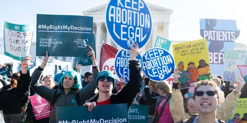 Abortion rights activists at a protest holding up signs.