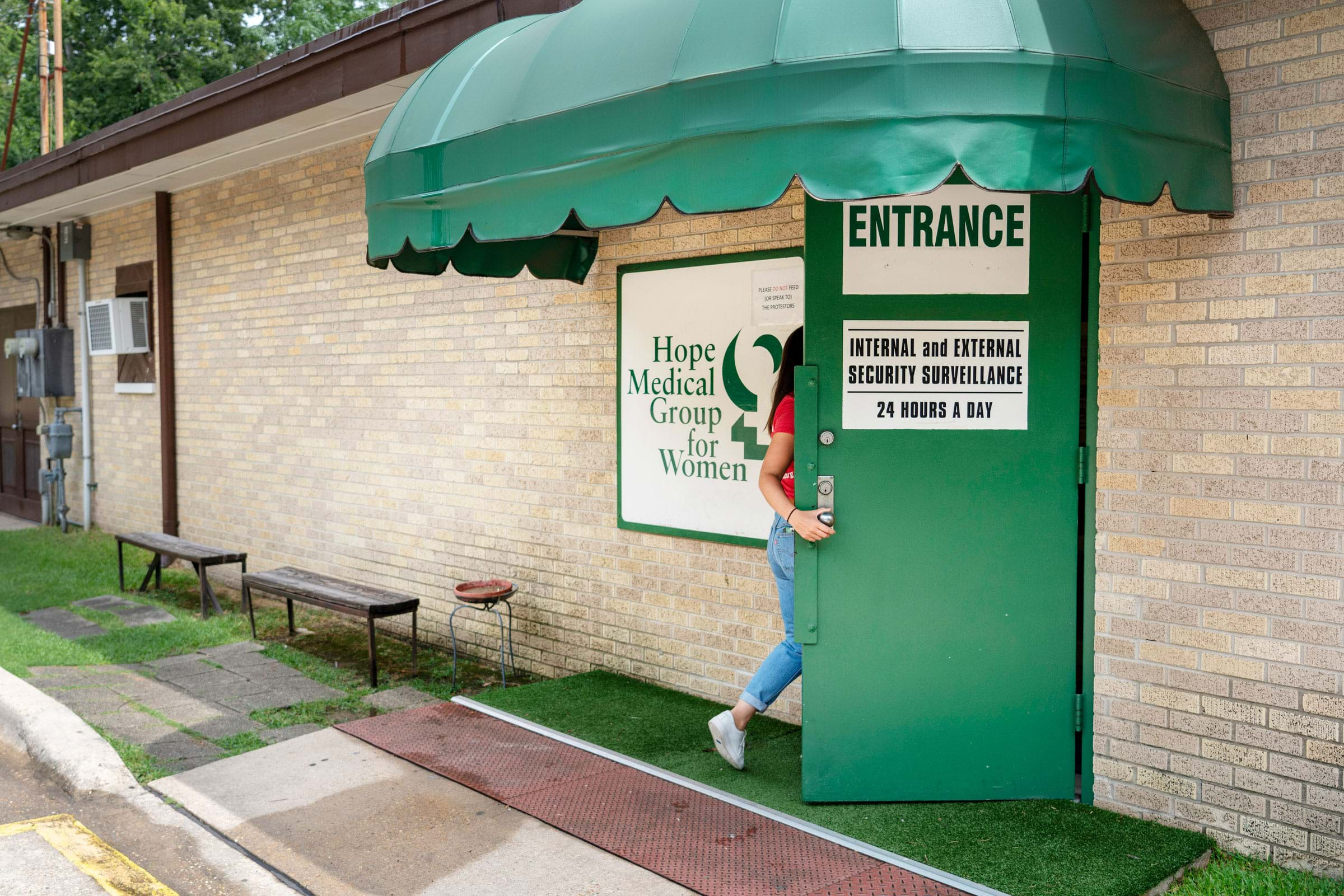 A woman entering the Hope Medical Group for Women under a green awning.