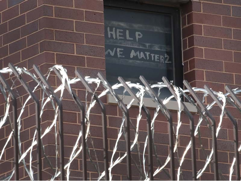 "A handmade sign that reads ""Help, we matter 2"" hang in a cell window of a prison guarded by barbed wire."