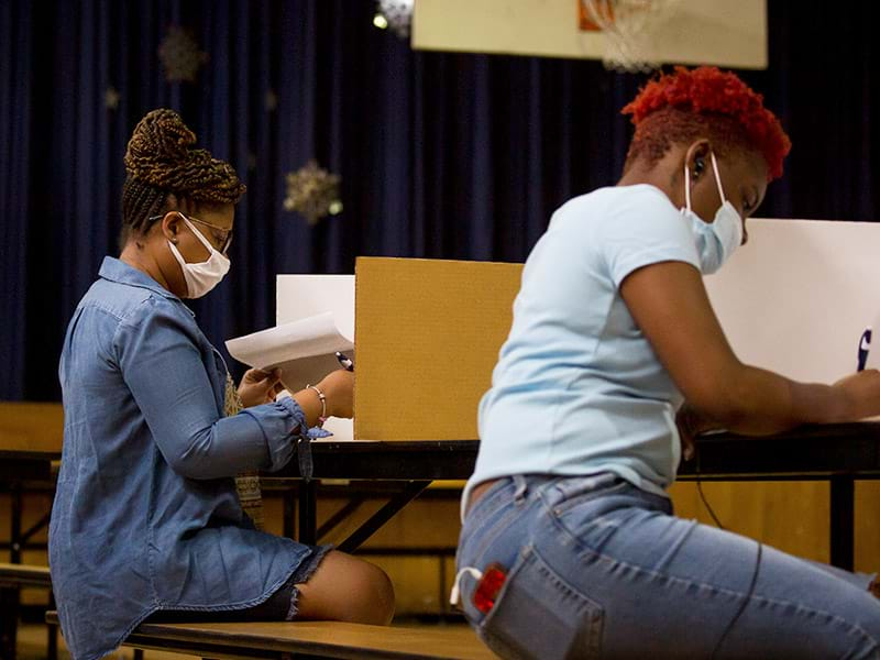 Two black women wearing protective masks and seated in a school gymnasium filling out ballots to vote.