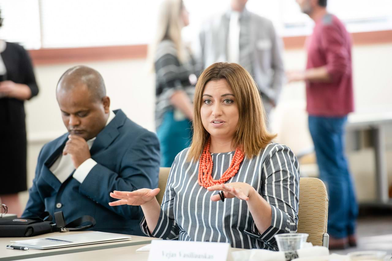 Katherine Perez, a Latina woman gesturing with her hands, is speaking at a round table discussion with The Coelho Law Fellows at Loyola Law School.  She is next to Abdurazak Kedir Abdu, a blind, African man who is one of the law fellows.