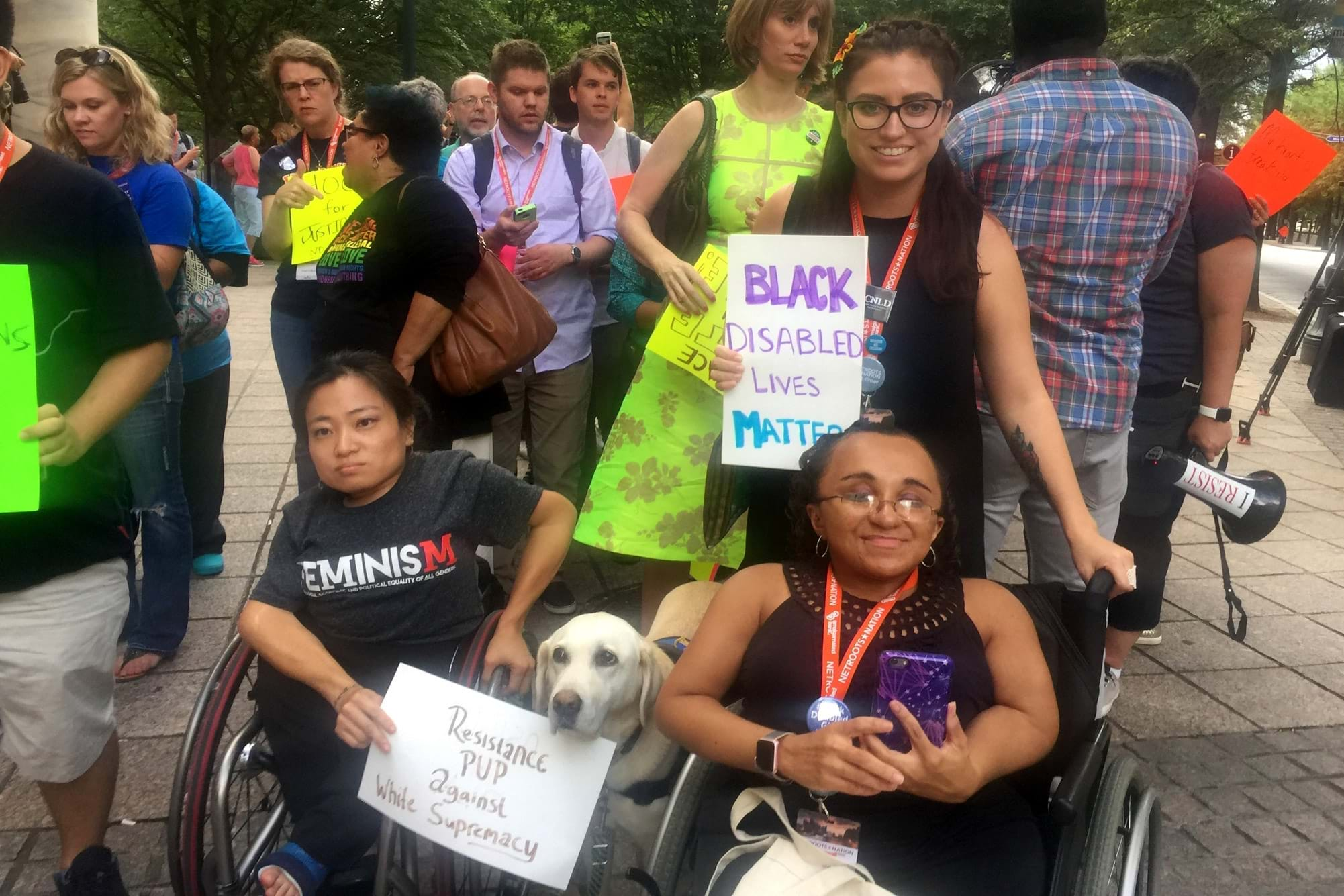 "Katherine Perez, a Latina woman holding a sign that reads ""Black Disabled Lives Matter"", is posing with two women.  Mia Ives-Rublee, an Asian woman in a wheelchair with a service dog holding a sign that reads ""Resistance Pup Against White Supremacy"" and Vilissa Thompson, a black disabled woman who uses a wheelchair.  Katherine, Mia and Vilissa are in Atlanta during a counter-protest to the Charlottesville neo-nazi / white supremacist rally that ended in a fatality."