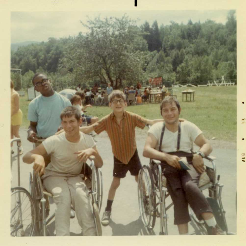 Four boys pose and smile for a photo on a sunny day. Two of them are in wheelchairs.
