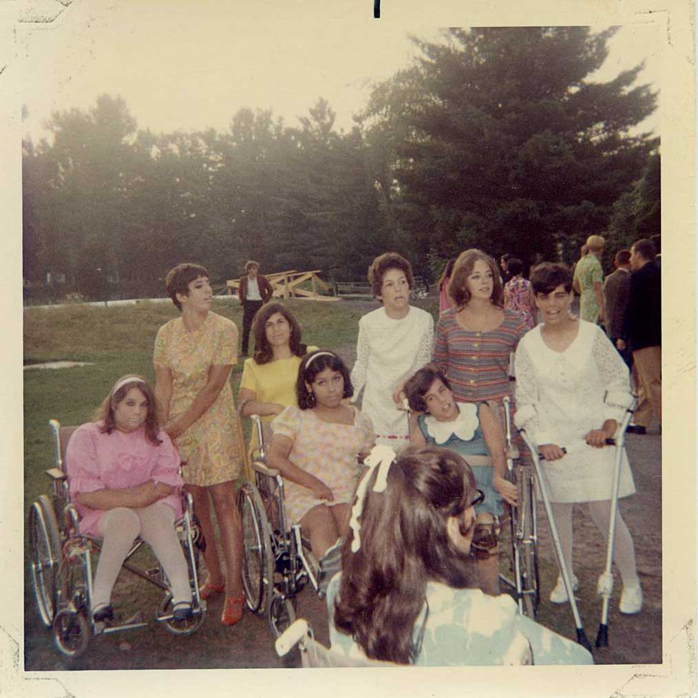 A group of young women, some in wheelchairs and others in crutches, gather for camp activities.