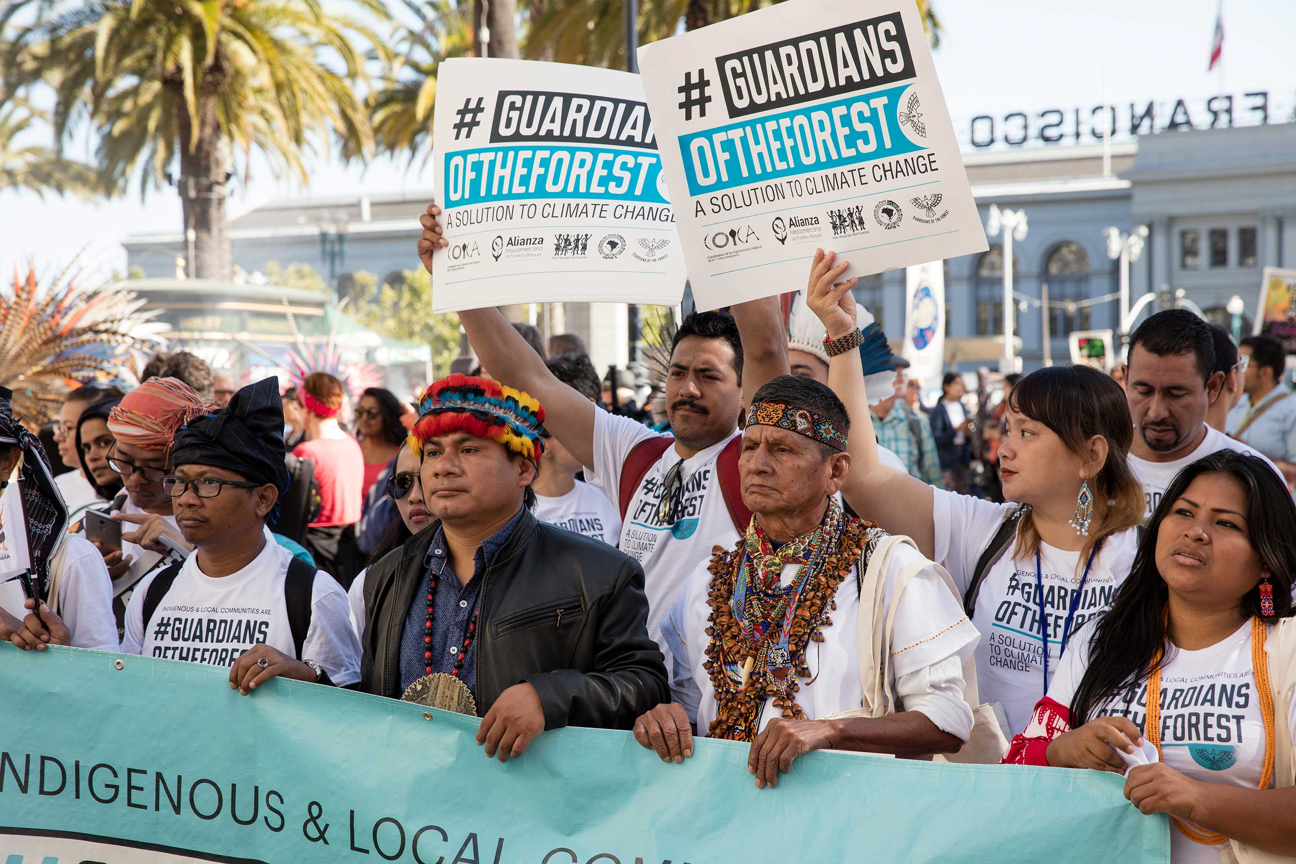 A group of indigenous leaders holds a large sign with the text Guardians of the forest during the 2018 Global Climate Action Summit  march in San Francisco.