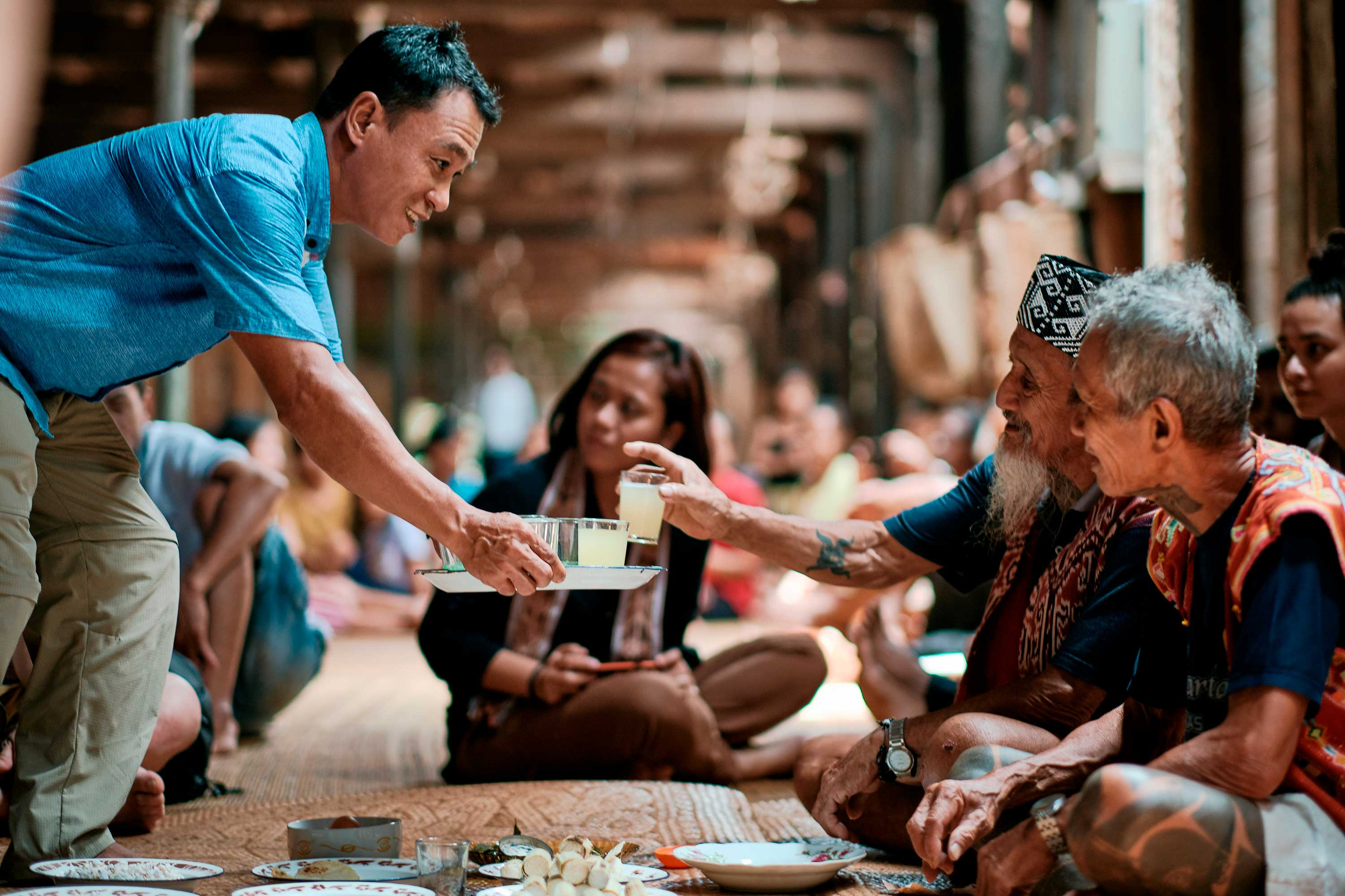 A man in a blue button-down shirt serves drinks to Sungai Utik elder Apai Janggut and another elder while perched on the floor of the longhouse main room.