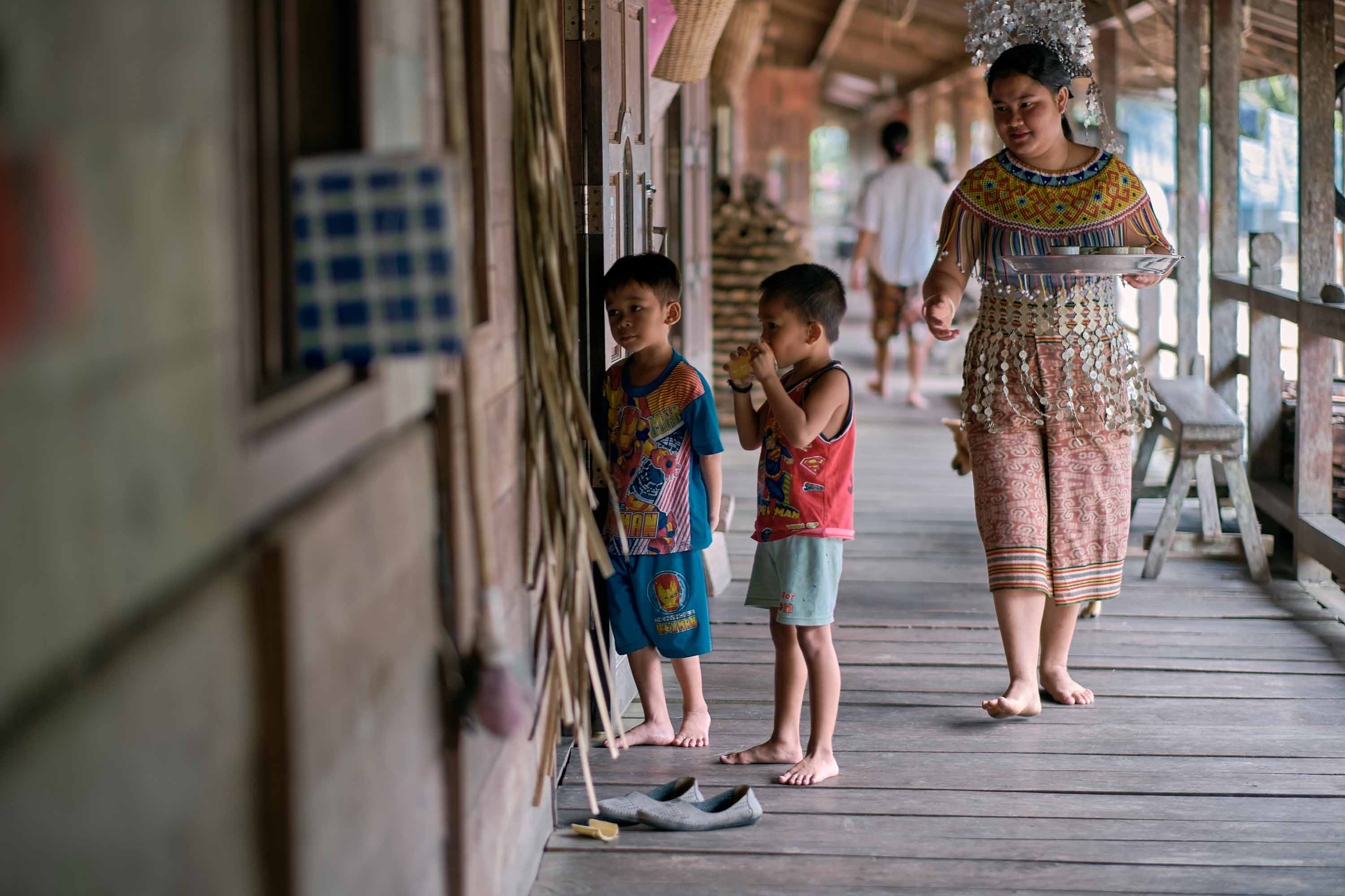 A woman in traditional Dayak Iban clothing holding a tray of drinks walks on the longhouse deck while two children peek into the main room.
