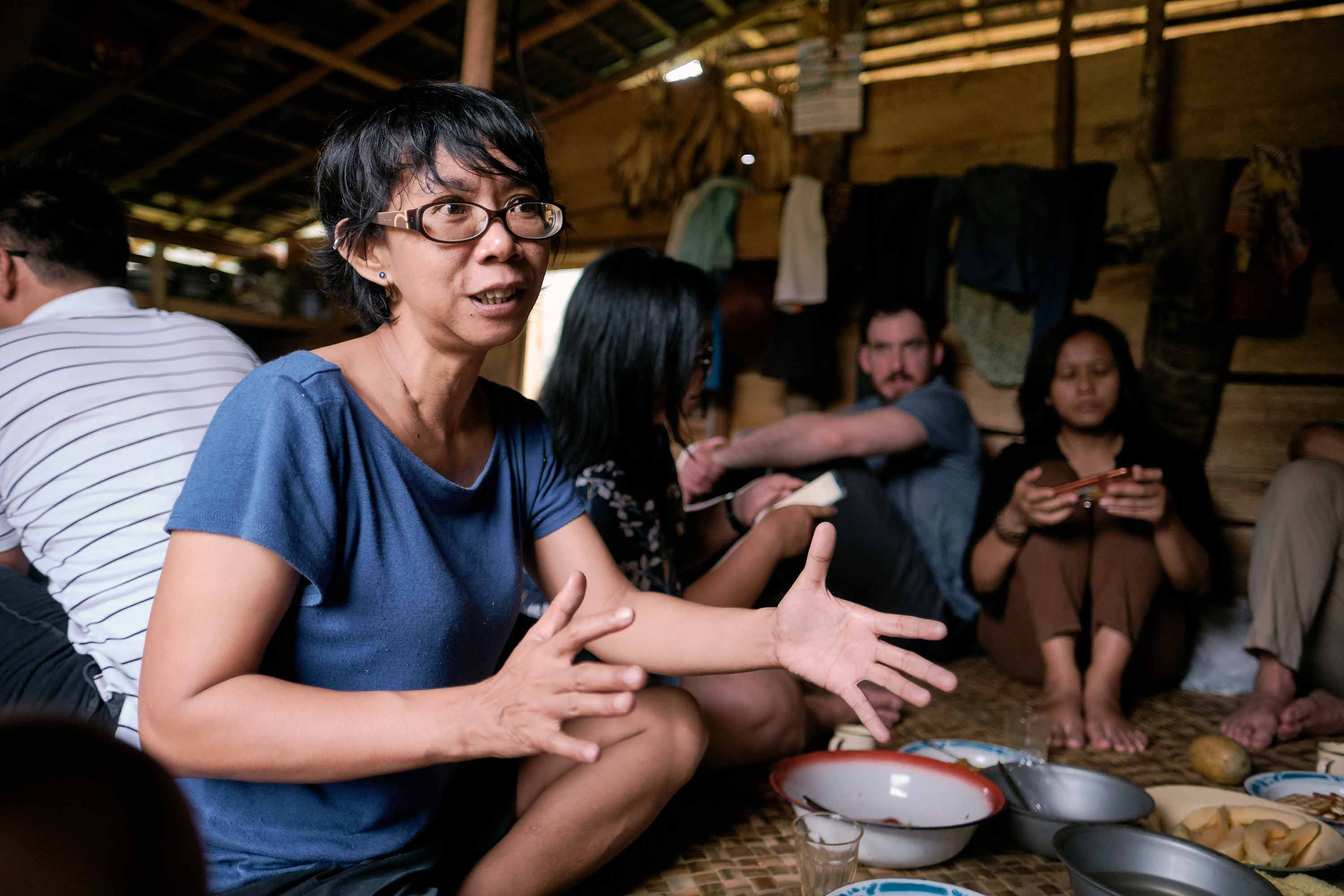A woman with short black hair and blue shirt extends her hand in gesture while sitting on the floor of a longhouse surrounded by plates of food.
