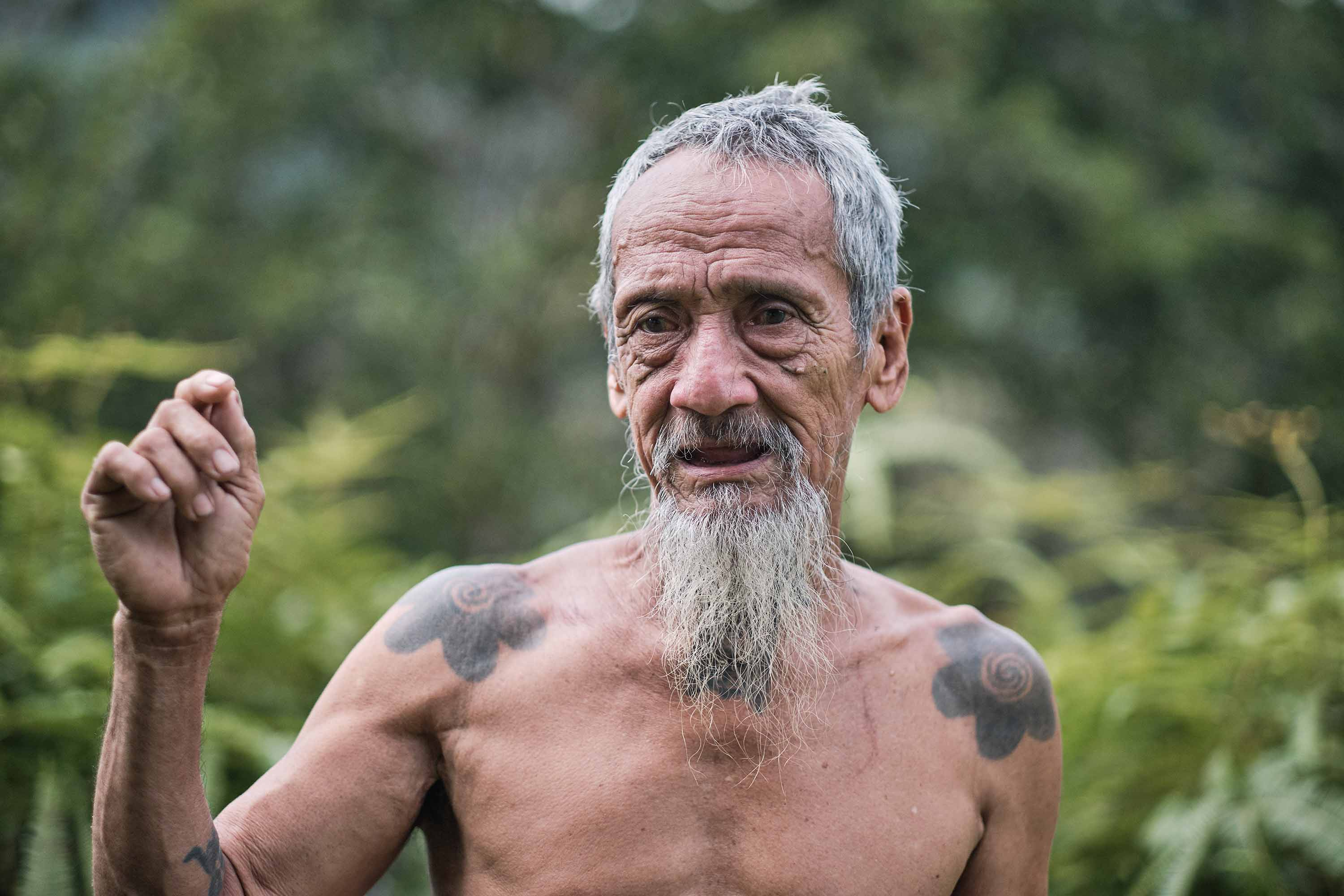A shirtless Apai Janggut in the forest with short gray hair, a long gray beard, and indigenous tattoos of flowers visible on both his shoulders.