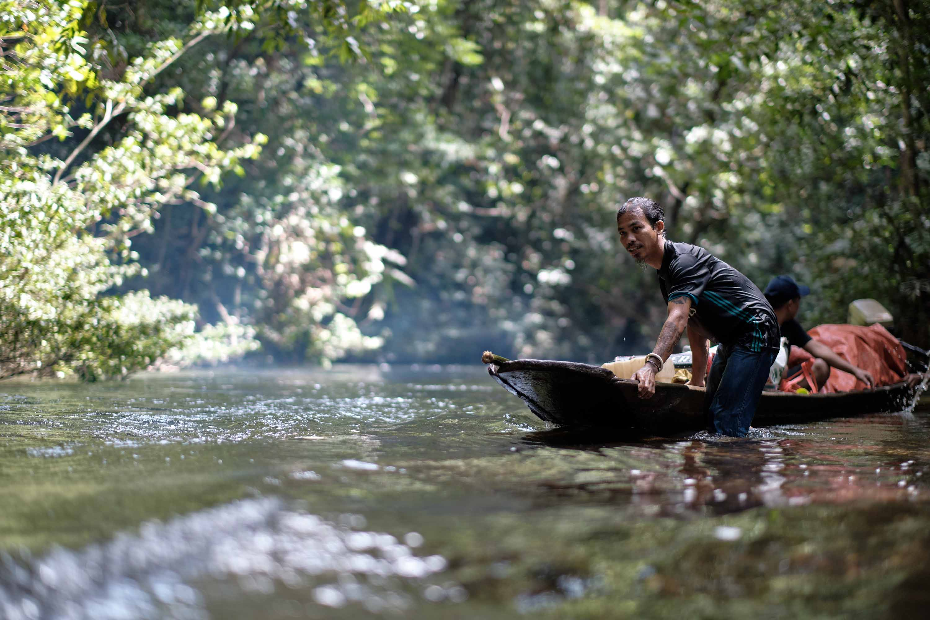 A man in black shirt and jeans pushes a canoe from a river bank in the middle of a dense forest.