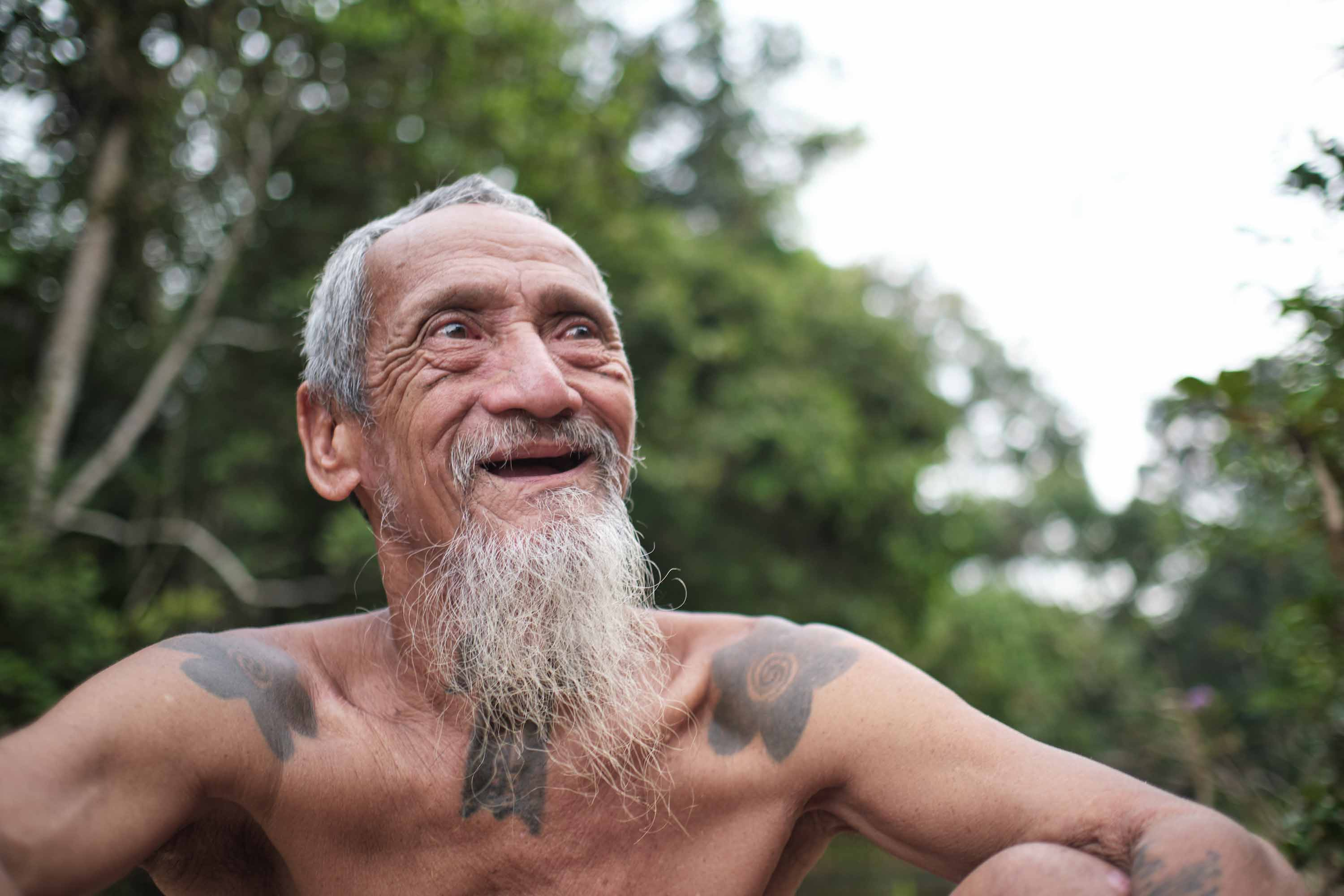 Shirtless Sungai Utik elder Apai Janggut with short gray hair and long gray beard smiles while looking off camera