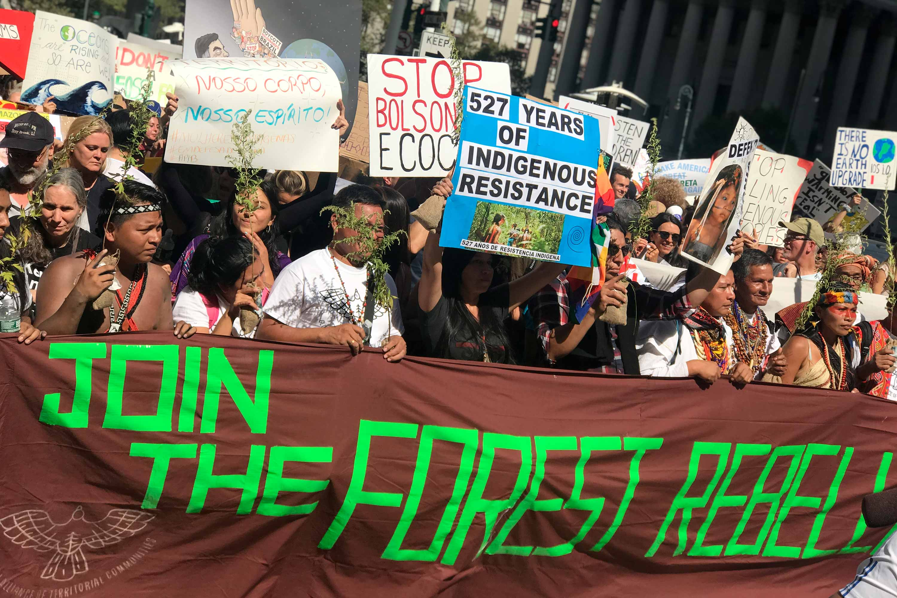 "A group of indigenous leaders holds a large brown textile with text ""Join the forest rebellion"" while marching down NYC during Climate Week 2019"