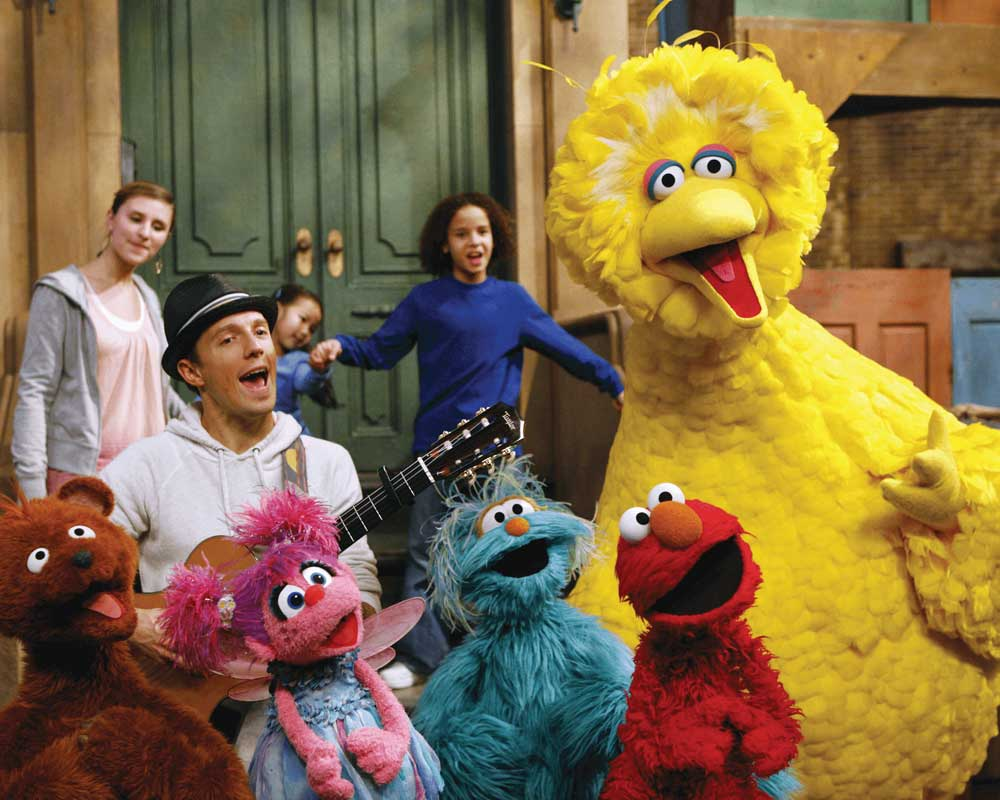 Jason Mraz sits on a stoop and serenades Big Bird, Elmo, and friends on Sesame Street.