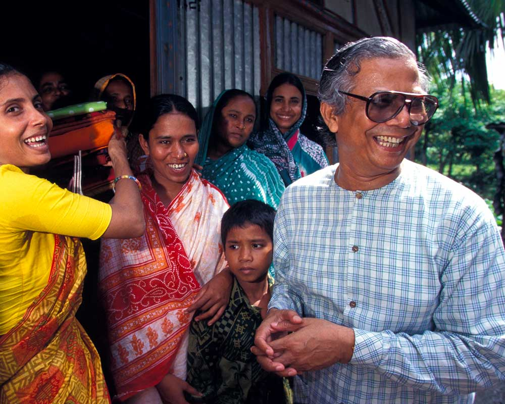 Muhammad Yunus in sunglasses looks to the right and smiles, surrounded by smiling people in a doorway.