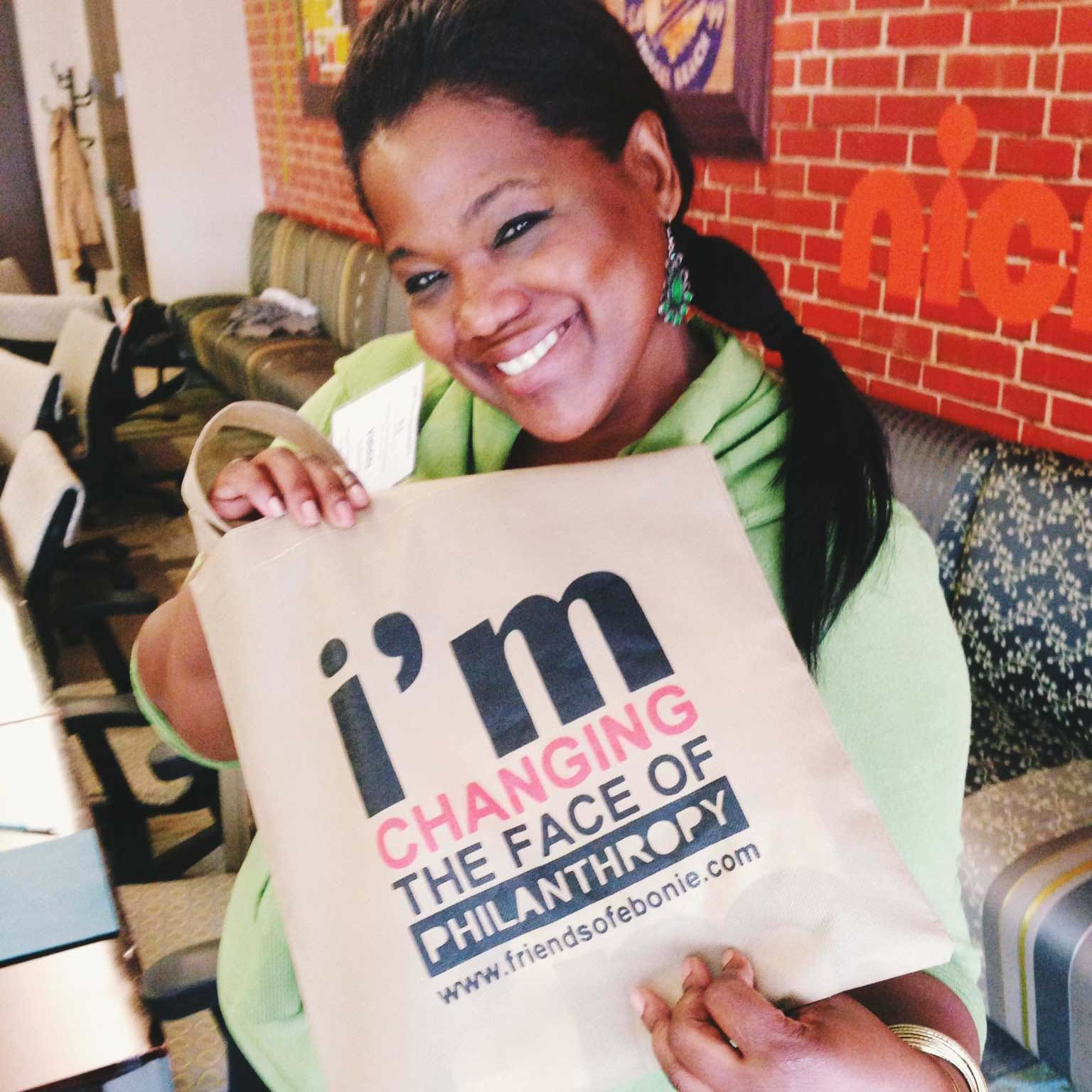 "Valaida Fullwood, a Black woman in a light green sweater and a ponytail, holds up a tote bag that reads ""I'm changing the face of philanthropy."""